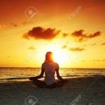 11409003-sunset-yoga-woman-on-sea-coast-Stock-Photo